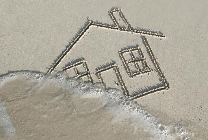 un dessin de maison sur une plage se faisant effacer par une vague